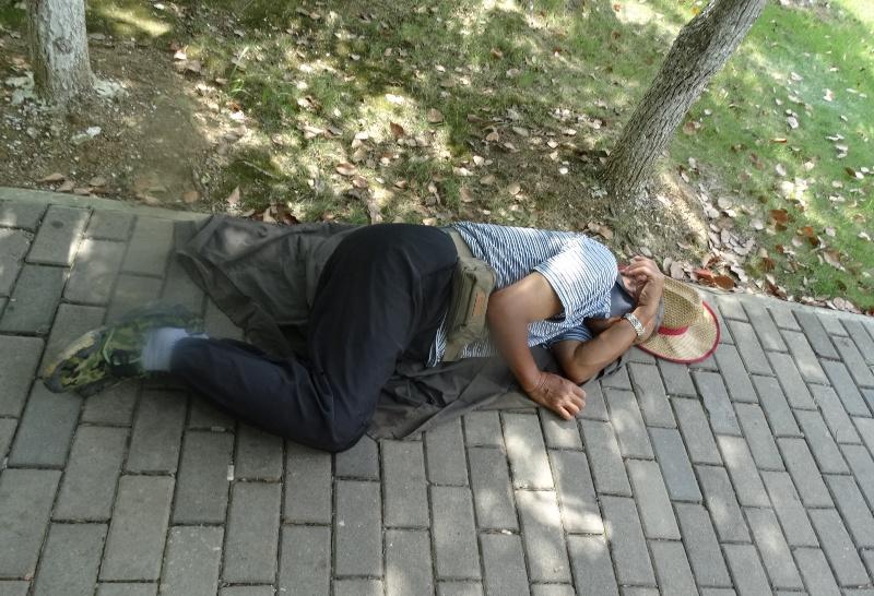 спит на тротуаре